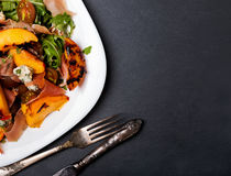 Dark style photo of delicious salad with grilled peaches and pro Stock Photography