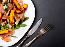 Dark style photo of delicious salad with grilled peaches Royalty Free Stock Photo