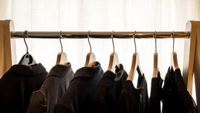 Dark suit jackets on hangers in front of a white background stock image