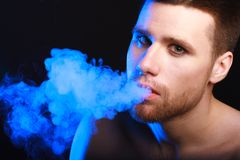 Dark and sullen shot of a young man. Smoking over a black background stock photo