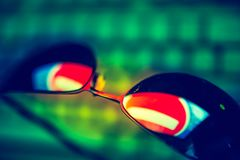 Dark sunglasses with reflection of a prohibiting road sign against a computer keyboard in the dark. The concept of anonymity in the Internet. Hacker activity royalty free stock photo