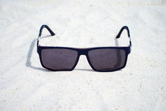 Dark Sunglasses on the sand Royalty Free Stock Photos