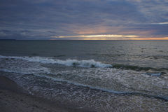 Dark sunset at the Baltic sea. Waves lapping on a sandy shore, a narrow strip of sunset glows on the horizon Stock Images