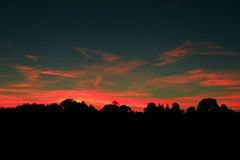 Dark sunset with crimson clouds. In the sun beams Royalty Free Stock Photos