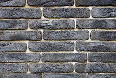 Dark texture of black bricks on the wall of the building. Stone dark background of black bricks on the wall of the building Royalty Free Stock Image