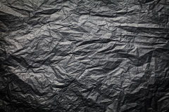 The dark texture of crumpled paper, black background stock photography