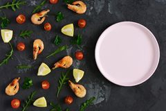 On a dark textured background there is an empty pink plate. From the edge of the scattered products. Shrimp, lemon and. Greens. Mock up, space for text. Tinted stock photo