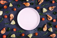 On a textured background there is an empty pink plate, food is scattered around. Shrimp, lemon and greens. Mock up. On a dark textured background there is an royalty free stock photos