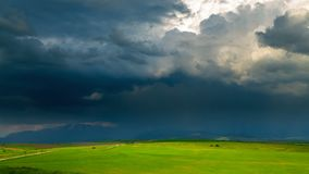 Dark thunderclouds over lighted spring fields stock footage