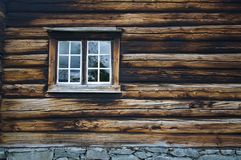 Dark timbered wooden wall with window. Dark country timbered wooden loghouse wall with window Stock Image