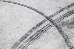 Dark tire tracks on gray asphalt road. Abstract transportation background with dark tire tracks on gray asphalt road Stock Photos