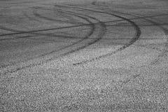 Dark tire tracks on gray asphalt road. Abstract transportation background with dark tire tracks on gray asphalt road Stock Image