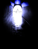 From the Dark to the Light of Jesus. Long tunnel walkway with white light and Jesus standing at the end Royalty Free Stock Images