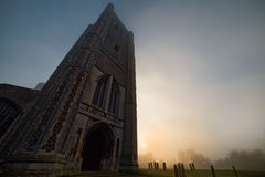 Dark Tower and Graveyard in Misty Sunrise. The huge dark tower of Wymondham Abbey in Norfolk is pictured in winter fog as the sun rises over the graveyard royalty free stock photography