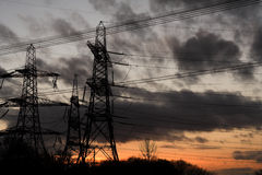 Dark towers. Pylon towers at sunset, silhouette of uk electricity pylons stock photos