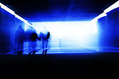 Dark tunnel. People walking towards the glowing entrance of a dark passage - a long expsure and zoomed shot Royalty Free Stock Photo