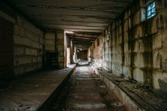 Dark tunnel in old abandoned brick factory. Abandoned industrial corridor Royalty Free Stock Images