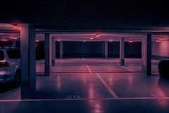 Dark underground car parking deck with neon red light.  royalty free stock photography
