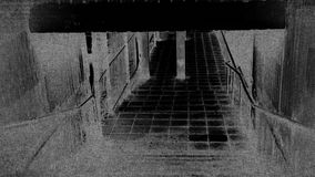 Dark Underpass. Walking down steps through an underpass with added digital noise and flickering stock video footage