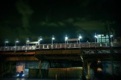 Dark urban Chicago city scene at night. With an elevated train platform, person, car and alley Stock Image