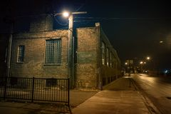 Dark urban city street and alleyway corner at night. Dark urban city street and alleyway corner with an industrial warehouse factory and an urban road leading Stock Photos
