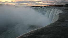 Dark view of Niagara Falls water in opposite to pink clouds of very early sunrise
