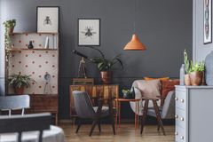 Dark vintage living room interior. Orange lamp above table and grey armchair in dark vintage living room interior with posters royalty free stock photo