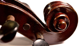 Dark violin scroll against white background, letterbox. Letterbox sized image of an extreme closeup of an antique violin's scroll and tuning pegs against a white Royalty Free Stock Photos