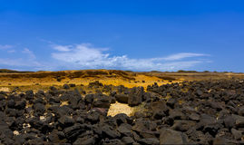 Dark volcanic rocks contrast against bright orange sands Stock Photo