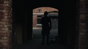 A German soldier walking slowly into a dark tunnel of an ancient red brick building. WWII reenactment. A dark walk way of a historic building reconstruction. An stock footage