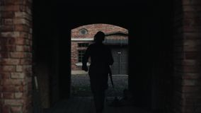 A German soldier walking slowly into a dark tunnel of an ancient red brick building. WWII reenactment. A dark walk way of a historic building reconstruction. An stock video footage