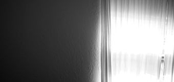 Dark wall with bright window light. A dark blank textured wall fills half the frame and on the right is a curtained window with bright sunlight shining through Royalty Free Stock Images