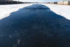 Dark water in polynya in Neva river in spring. Dark water in polynya in Neva river near The Palace Bridge in Saint Petersburg city in March Royalty Free Stock Image