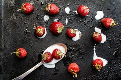 On a dark wet background spilled from a spoonful of yogurt and s. Prinkled with fresh strawberries, top view Stock Photo