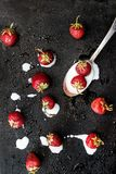 On a dark wet background spilled from a spoonful of yogurt and s. Prinkled with fresh strawberries, top view Stock Images