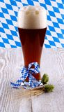 Dark wheat beer in glass with blue ribbon on white wood background Stock Photo