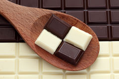 Dark and white chocolate in a wooden spoon. Close-up Stock Photos
