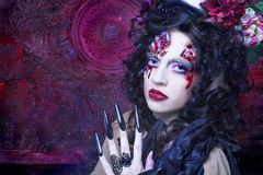 Dark Witch. Young woman in witch image with bloody makeup ann with skull Royalty Free Stock Photo