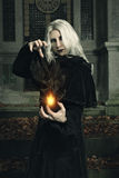 Dark witch manipulates fire Stock Photo