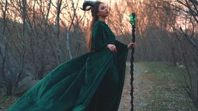Dark witch stands on forest path in long flying emerald dress free flying sleeves with a golden belt. lady with magic