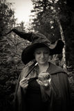 Dark witch with wand and glass ball. In hand royalty free stock photo
