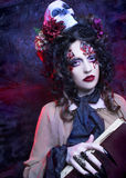 Dark Witch. Young woman in witch image with bloody makeup ann with skull Stock Images