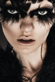 Dark woman with black feathers on eyes Royalty Free Stock Photos