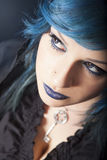 Dark woman with blue hair and lipstick. Key pendant. Dark girl Stock Images
