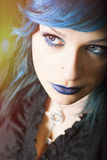 Dark woman with blue hair and lipstick. Key pendant. Dark girl. Girl with dark blue hair, blue lipstick. Key-shaped pendant around his neck. The woman is wearing royalty free stock photography