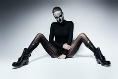 Dark woman with skull face on the floor. In studio Royalty Free Stock Photo