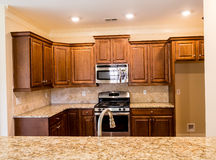 Dark Wood Cabinets and Granite Countertops. New kitchen with modern fixtures Royalty Free Stock Image