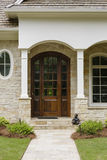 Dark wood door, with arches and a brick facade Stock Photo