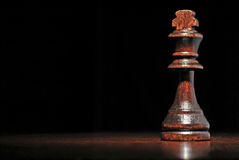 Dark wood king chess piece. Low angle view of a dark wood king chess piece on a reflective wooden surface against a dark background with copyspace stock photos