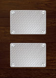 Dark wood metal plate. Two silver anti slip metal plate with screw with wooden wall Royalty Free Stock Images